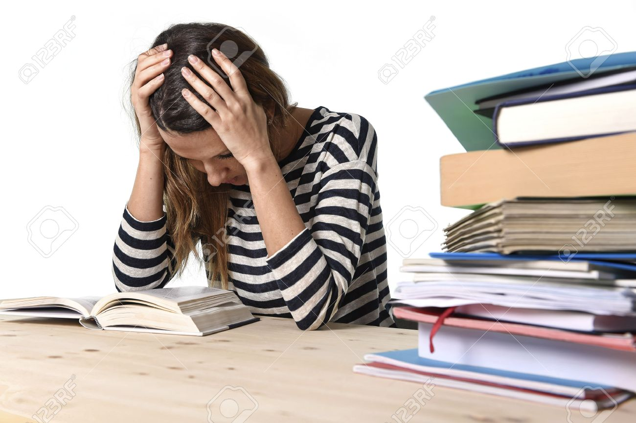 36900502 young stressed student girl studying pile of books on library desk preparing mba test or exam in str Stock Photo